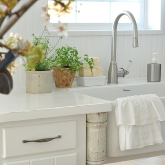 White Kitchen With Steal Faucet And Flowers