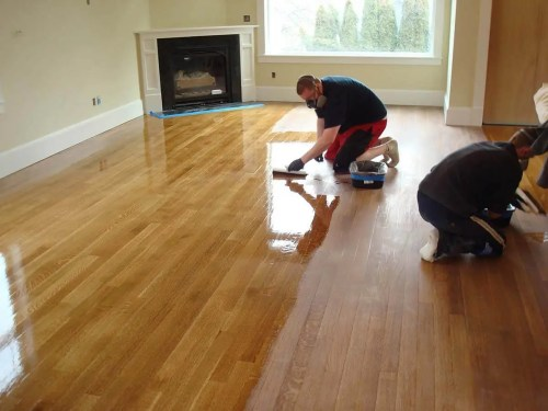 Contractors refinishing hardwood floor