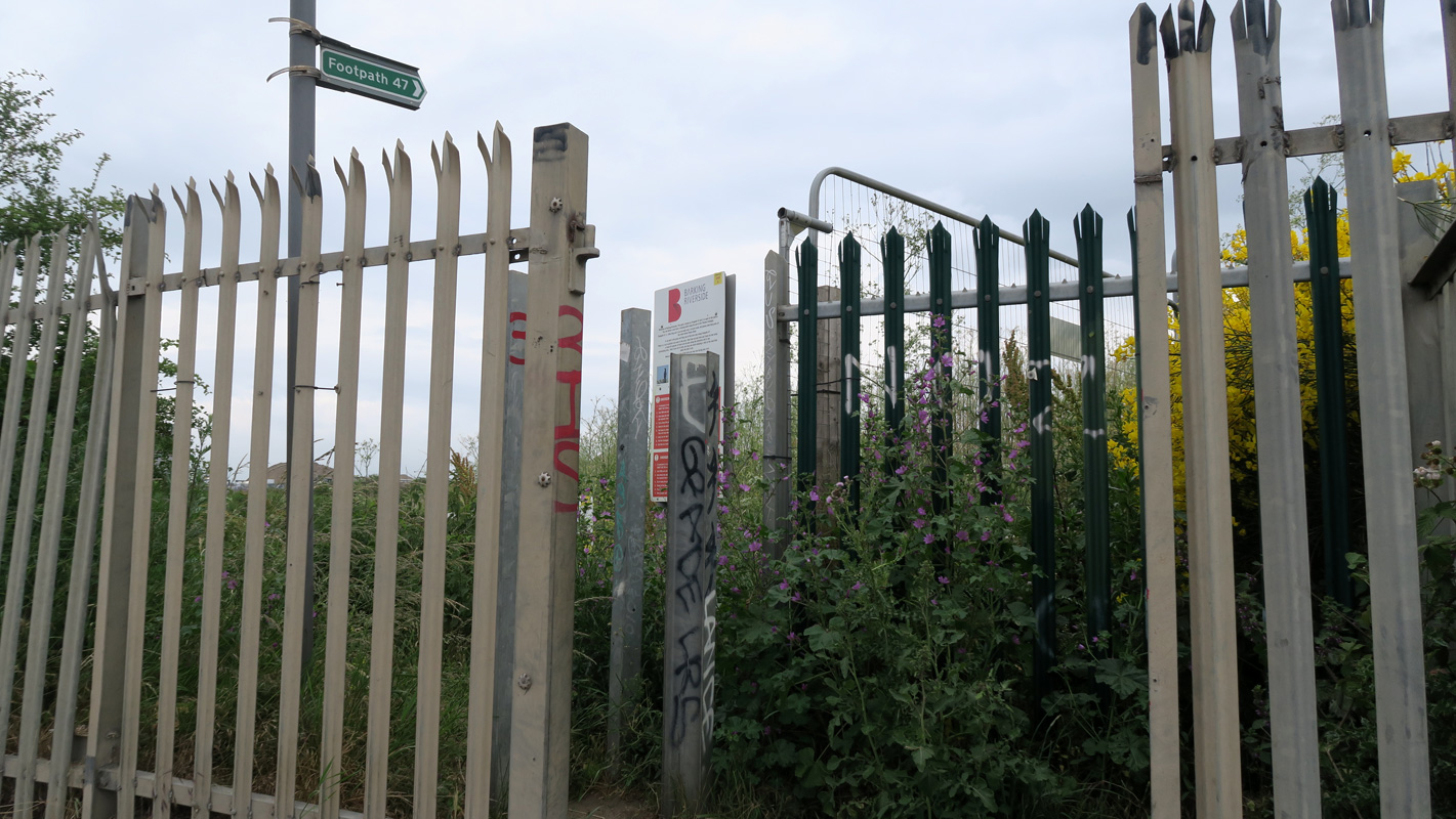 Tall spiked railings with a narrow gap, partially blocked by metal posts