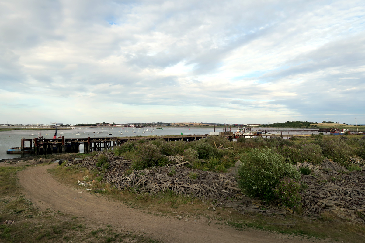 A dirt road curves around piles of broken concrete towards Coal Washer Wharf, a concrete wharf which sticks out and runs parallel with the shoreline, at Queenborough