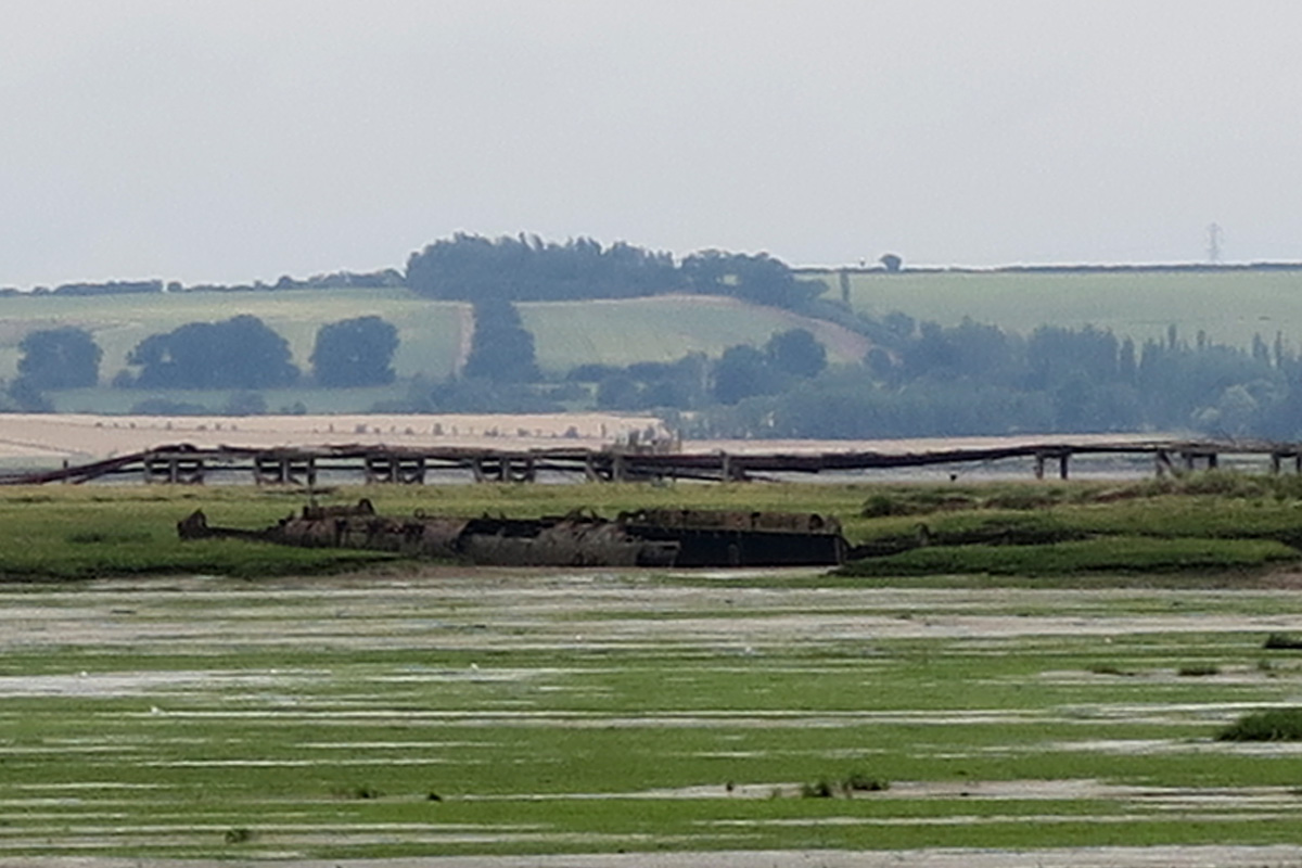 The long broken tube of a U Boat lying on the distant mud and marsh of Stoke Saltings