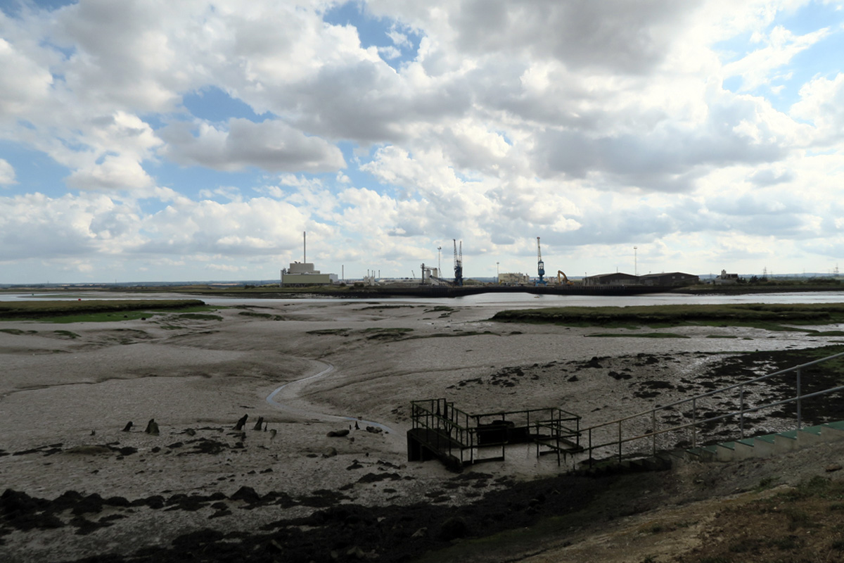 A muddy creek leads to the Swale, with industry beyond
