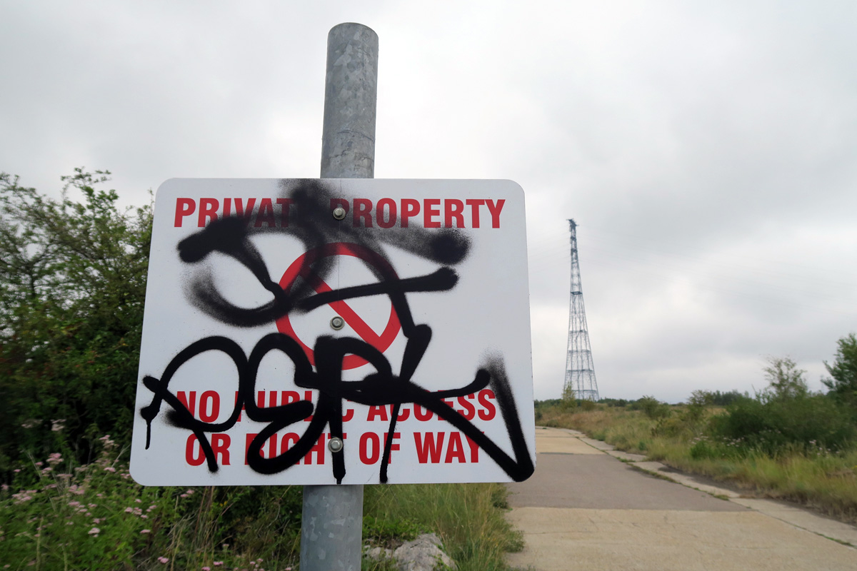 A wide concrete lane cutting straight across the landscape, with a graffitied 'keep out' sign