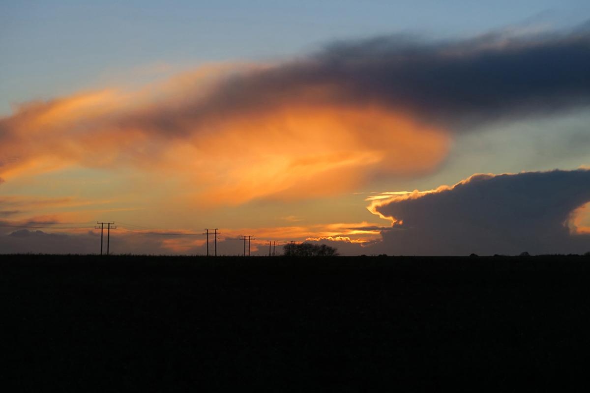 Clouds glowing orange and gold over a dark landscape. Paglesham.