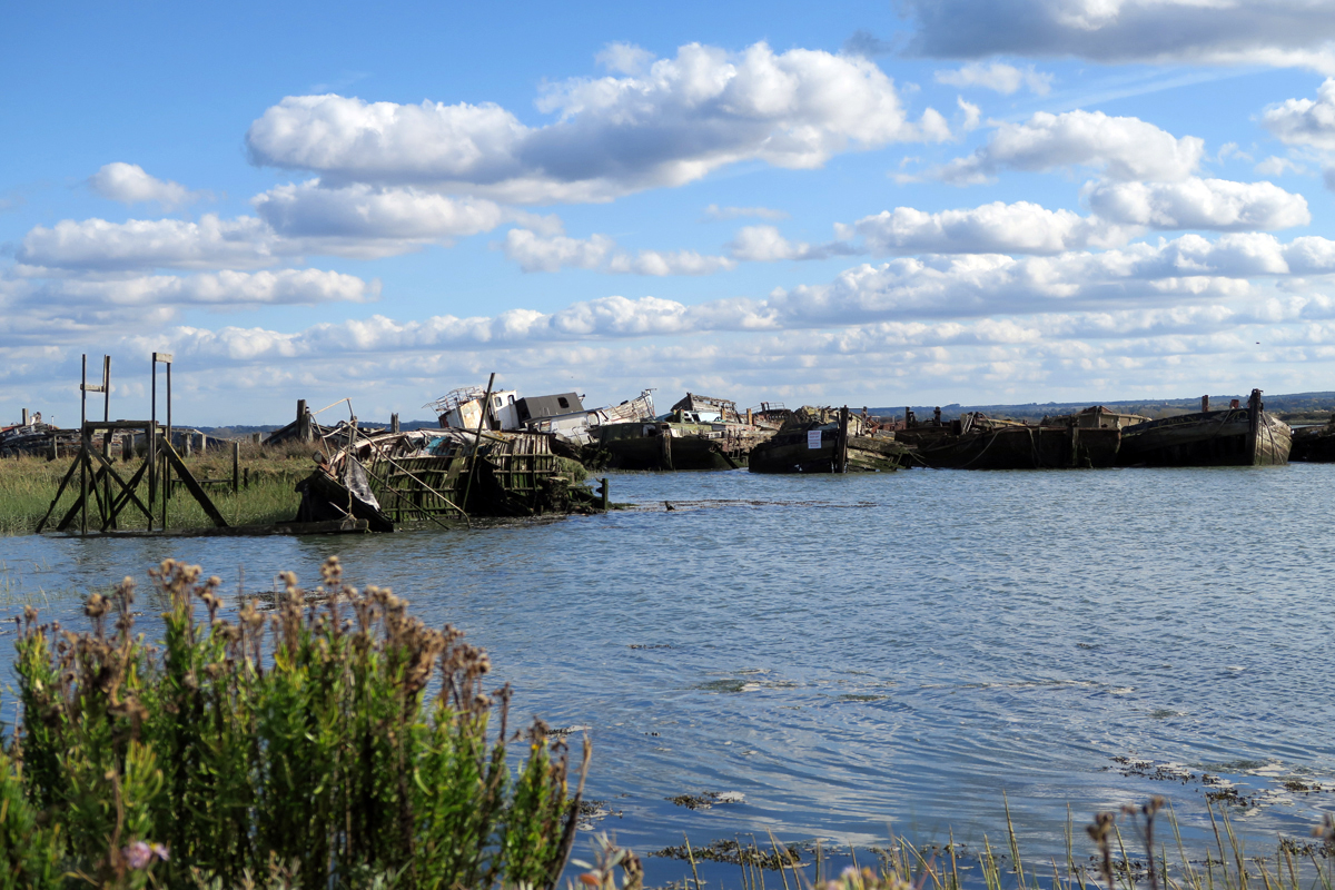 Tilted wooden wrecks are half submerged by the rising tide under a blue sky
