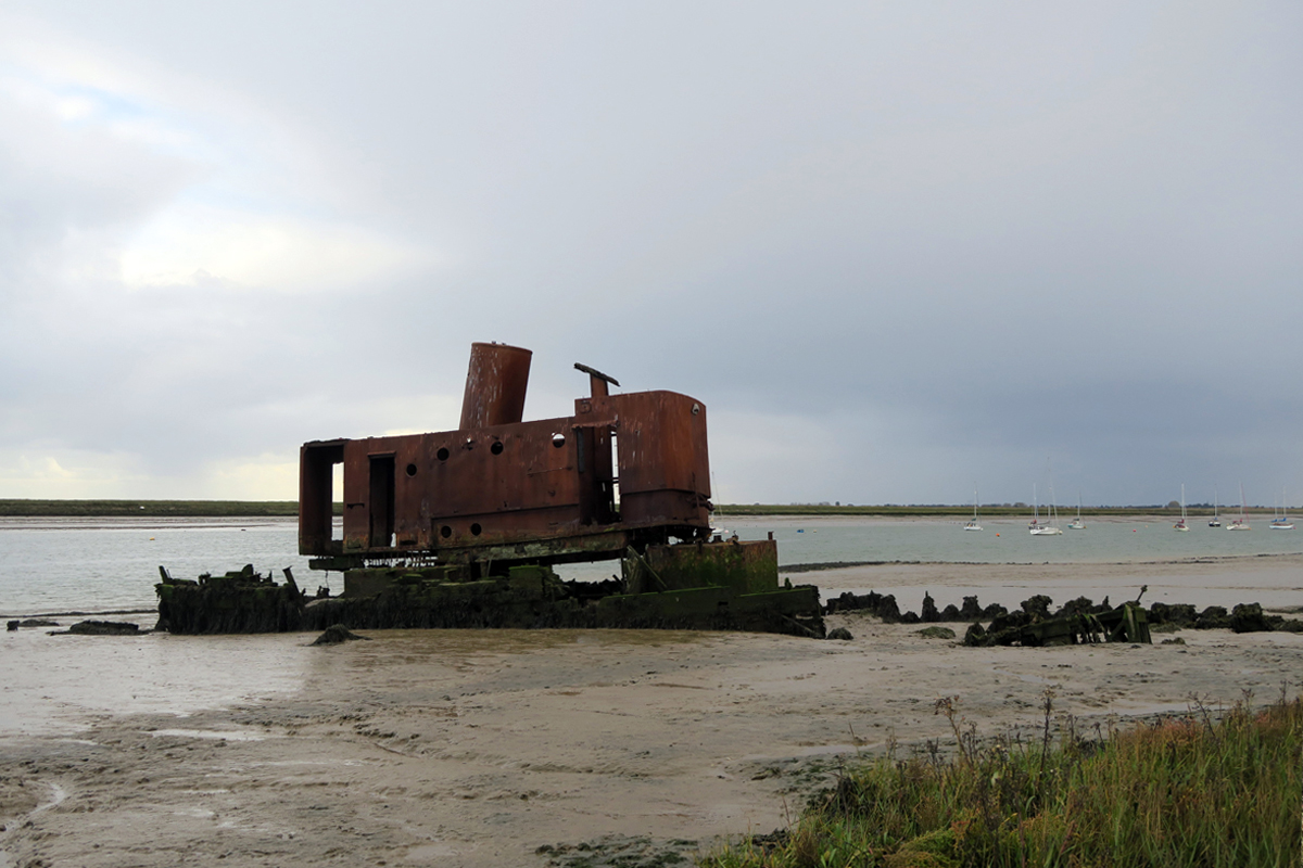 A large, rectangular metal box-like structure with a wide chimney stands upright amid the mostly rotted remnants of an old boat.