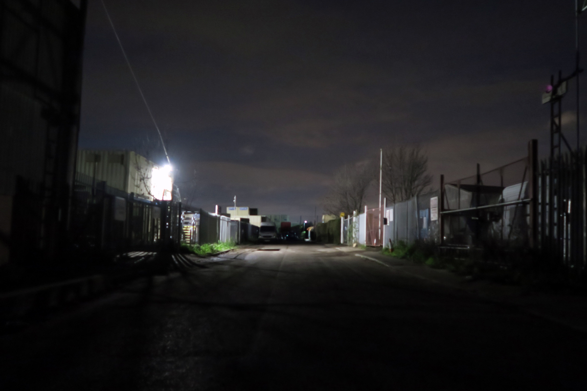 A wide, dark street through low industrial units and fencing, with a single light ahead
