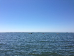 A study in blue, dotted by kayakers and one sailboat