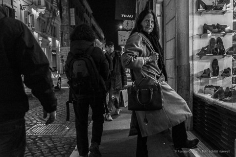 A woman on the sidewalk in Via del Corso. Nikon D810, 35 mm (35.0 mm ƒ/2) 1/160 ƒ/4 ISO 12800