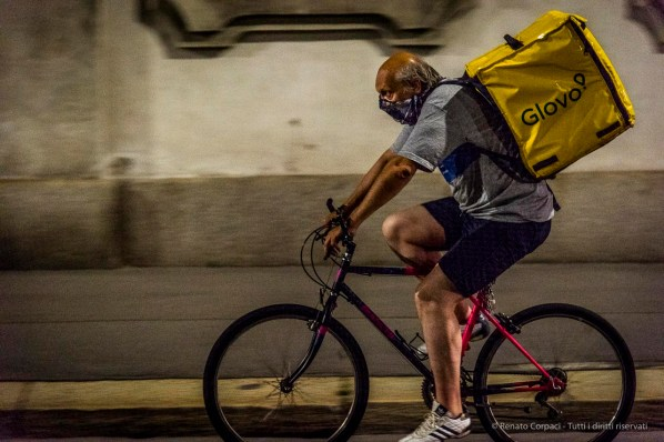 "Food Delivery. I feel a sense of uneasiness in front of this man wearing a bandana on his face, possibly to prevent to be casually recognized by acquaintances, former colleagues, relatives. A dignified man in very dire straits, on the brink of catastrophe... Milano, June 2018. Nikon D810, 95 mm (24-120 mm ƒ/4) 1/100"" ƒ/4.5 ISO 11400"