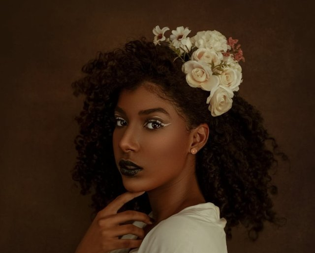 elegant black woman with creative makeup looking at camera