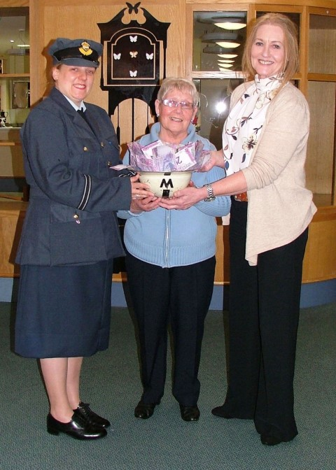 Susan McCann, from Renfrew Baths, in WW2 costume, left and Isobel Marshall, President of the pool's Over 50s Club present an ARP Warden's helmet full of cash to Jane Caldwell, from Erskine Hospital.