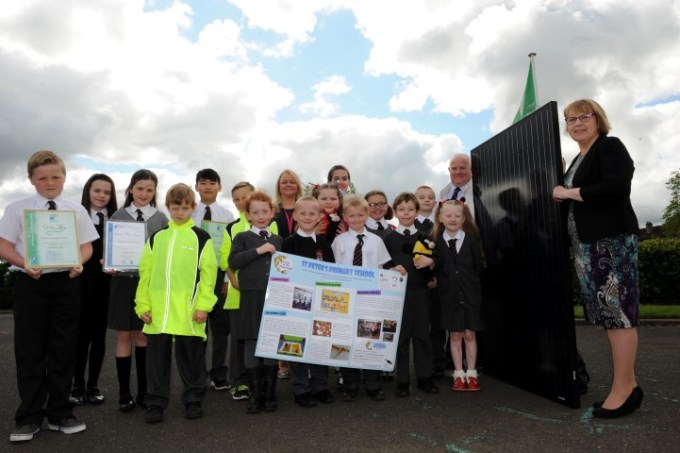 Councillors Eddie Devine and Jacqueline Henry (right) with head teacher Sharon Mazzoni and pupils from St Peter's Primary, Glenburn, with one of the new solar panels.
