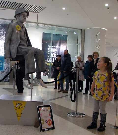 Four-year-old Chloe Morton, from Ardrossan looks on n amazement at floating human statue, ten-year-old Laughlan Muir.