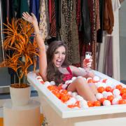 Fashionistas jump into a bath of kiddies play pit balls