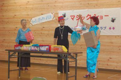 Mme Kikuchi est une magicienne. Pour distraire les enfants, elle et son association organisent des spectacles dans les écoles.