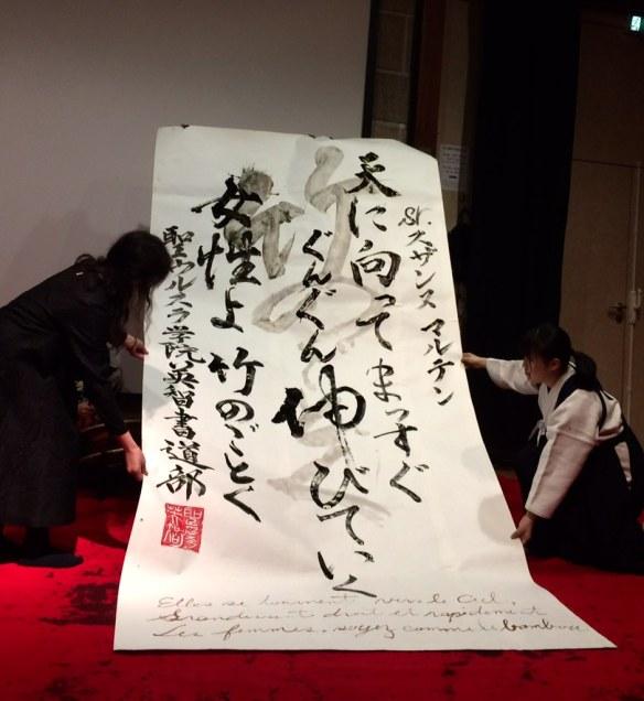 Madame Takahashi et les élèves présentent l'œuvre « comme les bambous » au public. On voit clairement la variété des teintes d'encre utilisées, ainsi que les kana-moji, mais aussi kanjis et la traduction en français qui y ont été dessinés.
