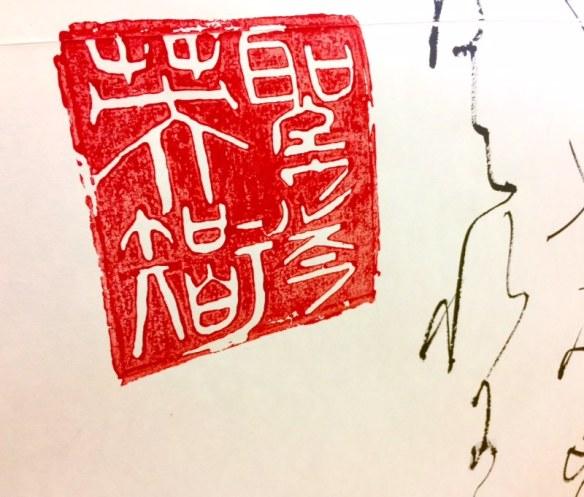 Vue en gros plan du sceau utilisé pour signer les œuvres. L'encre rouge n'est pas encore sèche partout.
