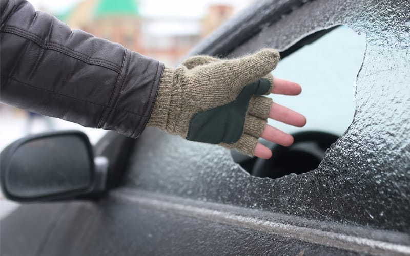 Thief's hand smashing an icy car window to break in