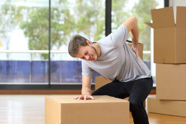 Man Suffering Back Ache Moving Boxes