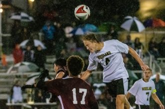 WATERBURY, CT. 07 November 2019-110719BS576 - Woodland's Nathaniel Smith (4) goes up high heading the ball in front of Naugatuck's Stephen Alziphat (17), during the NVL Boys Soccer final between Naugatuck and Woodland at Municipal Stadium in Waterbury on Thursday. The Naugatuck boys soccer team are the 2019 NVL Champions after beating Woodland 2-1. Bill Shettle Republican-American