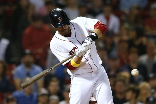 FILE - In this Sept. 7, 2019, file photo, Boston Red Sox's J.D. Martinez hits a solo home run during the ninth inning of a baseball game against the New York Yankees in Boston. Red Sox designated hitter Martinez has decided to keep his contract with the team instead of becoming a free agent again. (AP Photo/Michael Dwyer, File)