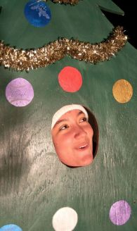 Jenna Campbell of Waterbury has her picture taken in a Christmas tree cutout during the annual Light Up Thomaston Christmas celebration in Thomaston Saturday. Steven Valenti Republican-American