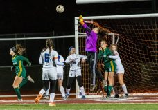 NAUGATUCK, CT. 20 November 2019-112019BS884 - Litchfield goalkeeper Molly Lennon leaps up and punches the ball out of the goalie area on a corner kick, during the Girls Soccer Class S semifinal match between Litchfield and Holy Cross at Naugatuck High School on Wednesday. Holy Cross beat Litchfield 3-1 and advances to the Class S final this Saturday. Bill Shettle Republican-American