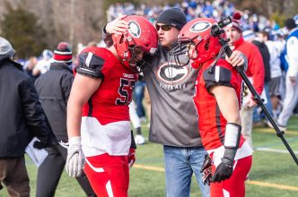CHESHIRE, CT. 28 November 2019-112819BS1271 - Steve Bergin father of a Cheshire player, center, consoles both Cheshire's Sean Cangiano (57), left, and Cheshire's Christian Russo (6), right, after Cheshire lost in double overtime to Southington 21-20, during a SCC game and the annual Cheshire vs Southington Thanksgiving game called the Apple Valley Classic at Cheshire High School on Thursday. Bill Shettle Republican-American