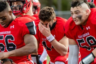 CHESHIRE, CT. 28 November 2019-112819BS1273 - Cheshire quarterback Jason Shumilla (14), center, reacts in disappointment on the field, as he and teammates Chisom Okoro (56), left, and William Bergin (59), right, all look on, after Cheshire lost to Southington 21-20 in double overtime, during a SCC game and the annual Cheshire vs Southington Thanksgiving game called the Apple Valley Classic at Cheshire High School on Thursday. Bill Shettle Republican-American