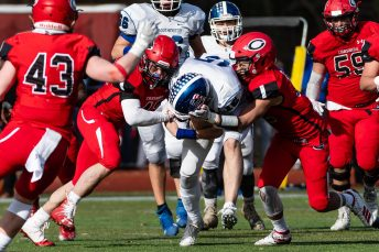 CHESHIRE, CT. 28 November 2019-112819BS1258 - Cheshire's Jacob Dubois (42), left, and Cheshire's Nicholas DiDomizio (12) right, gang tackle Southington quarterback Brady Lafferty (15), center, during a SCC game and the annual Cheshire vs Southington Thanksgiving game called the Apple Valley Classic at Cheshire High School on Thursday. Southington won 21-20 in double overtime. Bill Shettle Republican-American