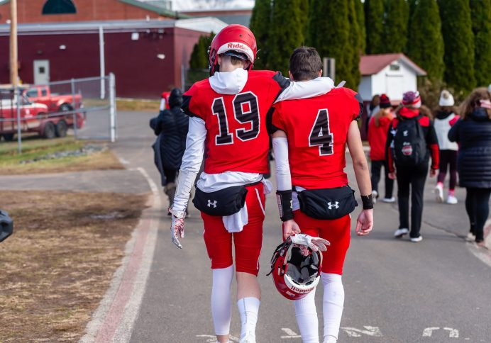 CHESHIRE, CT. 28 November 2019-112819BS1277 - Cheshire players Thomas Graikoski (19) and Nick Valente (4) walk off the field toward the locker room after Cheshire lost in double overtime 21-20 to Southington, during a SCC game and the annual Cheshire vs Southington Thanksgiving game called the Apple Valley Classic at Cheshire High School on Thursday. Bill Shettle Republican-American