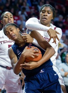 Connecticut guard Aubrey Griffin, left, is fouled by Temple forward Shantay Taylor during the second half of an NCAA college basketball game Sunday, Nov. 17, 2019, in Philadelphia. Connecticut won 83-54. (AP Photo/Laurence Kesterson)
