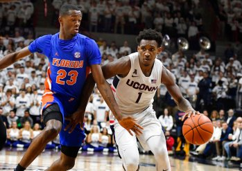 Connecticut's Christian Vital, right, is guarded by Florida's Scottie Lewis, left, during the second half of an NCAA college basketball game, Sunday, Nov. 17, 2019, in Storrs, Conn. (AP Photo/Jessica Hill)