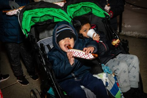 WATERBURY, CT. 08 December 2019-120819BS13 - Adrian Rivera, 3, takes a bite out his Frankies Hot Dog, left, as his brother Nate, 5, enjoys a cup of Hot Chocolate, during the the annual lighting of the Christmas Tree and the surrounding lights on the City Green to help launch the Holiday Season in downtown Waterbury on Sunday. The lighting ceremony was pushed backed on week due to the snowstorm last weekend. Bill Shettle Republican-American