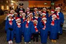 WATERBURY, CT. 08 December 2019-120819BS15 - Detective Andrea Saunders, back left, stands with the PAL Children's Chorus, during the the annual lighting of the Christmas Tree and surrounding lights on the City Green to launch the Holiday Season in downtown Waterbury on Sunday. Bill Shettle Republican-American