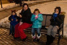 WATERBURY, CT. 08 December 2019-120819BS13 - Michelle Cintron, second from left, sits with her children Eduardo Bosques, 2, left, Marlina Bosques, 5, and her niece Vanessa Bosques, 8, as they sip on some hot chocolate waiting for Santa to arrive, during the the annual lighting of the Christmas Tree and the surrounding lights on the City Green to help launch the Holiday Season in downtown Waterbury on Sunday. The lighting ceremony was pushed backed on week due to the snowstorm last weekend. Bill Shettle Republican-American