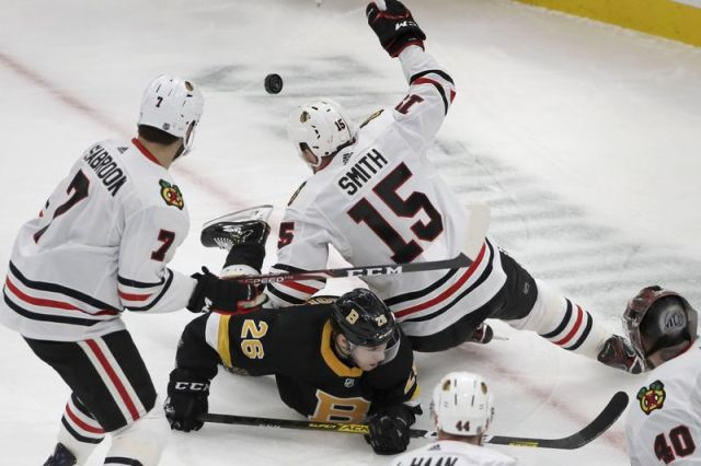 Boston Bruins center Par Lindholm (26) goes down as he competes for the puck against Chicago Blackhawks center Zack Smith (15) in the first period of an NHL hockey game, Thursday, Dec. 5, 2019, in Boston. (AP Photo/Elise Amendola)