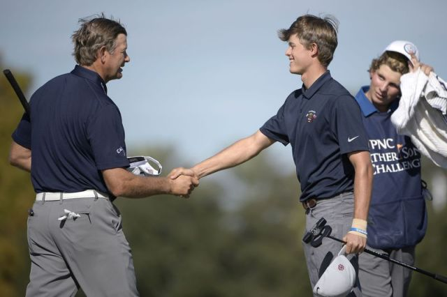 Retief Goosen, left, of South Africa, shakes hands with his son, Leo Goosen, after finishing on the 18th green during the first round of the Father Son Challenge golf tournament Saturday, Dec. 7, 2019, in Orlando, Fla. (AP Photo/Phelan M. Ebenhack)