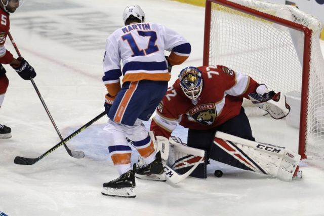 Florida Panthers goaltender Sergei Bobrovsky (72) stops the puck as New York Islanders left wing Matt Martin (17) looks on during the third period of an NHL hockey game, Thursday, Dec. 12, 2019, in Sunrise, Fla. The Islanders won 3-1. (AP Photo/Lynne Sladky)