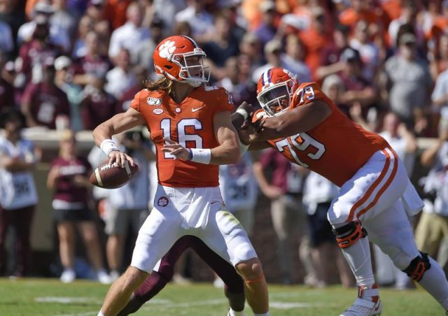 File-This Sept. 7, 2019, file photo shows Clemson quarterback Trevor Lawrence dropping back to pass with blocking help from Jackson Carman (79) during the second half of an NCAA college football game in Clemson, S.C. Carman is one of the few recent five-star recruits from Ohio who didn't end up at Ohio State. Now the two schools meet in the CFP semifinals, where Carman will be matched up against Ohio State's star defensive lineman Chase Young. (AP Photo/Richard Shiro, File)