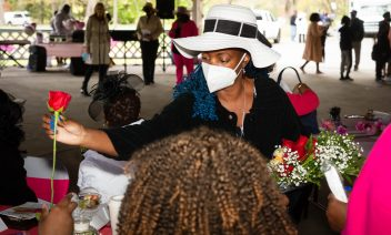 Patricia Sands, a member of the Black Women United Committee, hands out roses to all the ladies in attendance during a Mother's Day celebration held Saturday at Lakewood Park in Waterbury. Jim Shannon Republican American