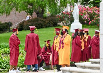 Sacred Heart graduates sit outside as they get get ready for the start of the 99th annual commencement exercises for Sacred Heart High School Friday at The Basilica of the Immaculate Conception in Waterbury. Jim Shannon Republican American