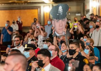 Shelby Iava of Watertown, holds up a big head photo of Waterbury Police recruit Anthony Batista during basic training graduation ceremonies for the Waterbury Police Academy Class 2020-01 Tuesday at the Palace Theater in Waterbury. Jim Shannon Republican American