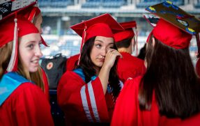 Northwestern Regional High School graduate Kelly Oberheim wipes away a tear as she gathers with her classmates prior to graduation ceremonies Wednesday at Dunkin' Donuts Park in Hartford. Jim Shannon Republican American
