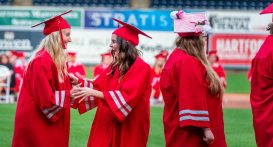 Northwestern Regional High School graduates Marisa Montano, left, and Caroline Mona have a hard time containing their excitement while waiting to receive their diploma during graduation ceremonies Wednesday at Dunkin' Donuts Park in Hartford. Jim Shannon Republican American
