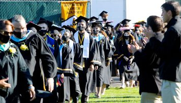 Graduate's march into their ceremony during the Waterbury Career Academy graduation at Municipal Stadium in Waterbury Wednesday. Steven Valenti Republican-American