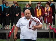 Alex Gomez, the father of the late Kristopher Gomez makes his way back to his seat after being presented with a diploma, cap and gown and a yearbook as his son was remembered during graduation ceremonies on the Torrington High School football field on Friday. Kristopher was a junior and only 16-years-old when died in 2020 after suffering a stroke. Jim Shannon Republican American
