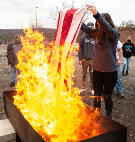 Sabrina Howard, 15, a member of the Naugatuck High School Air Force JROTC, places a portion of an American flag into the fire during a flag disposal ceremony held Nov. 12, 2020, in Naugatuck. The event was hosted by the Naugatuck Veterans Council, the Naugatuck High School Air Force JROTC and Sons of The American Legion Squadron 17. The ceremony to retire the flags is held twice a year. (Jim Shannon Republican-American)