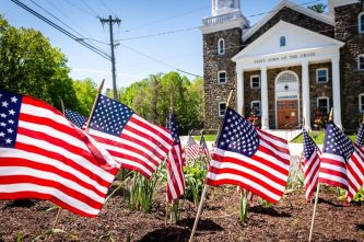 U.S. flags wave in the wind as they dot the landscape in front of St. John of the Cross Church in Middlebury for Memorial Day 2020. (Bill Shettle Republican-American)